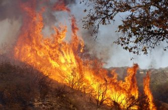 MALIBU, CA - NOVEMBER 11: A wildfire burns at the Salvation Army Camp on November 10, 2018 in Malibu, California. The Woolsey fire has burned over 70,000 acres and has reached the Pacific Coast at Malibu as it continues grow.   Sandy Huffaker/Getty Images/AFP