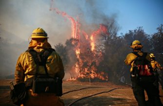 MALIBU, CA - NOVEMBER 11: Firefighters battle a blaze at the Salvation Army Camp on November 10, 2018 in Malibu, California. The Woolsey fire has burned over 70,000 acres and has reached the Pacific Coast at Malibu as it continues grow.   Sandy Huffaker/Getty Images/AFP