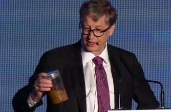 """Microsoft founder Bill Gates (R) talks while holding a container (L) with human feces during the """"reinvented toilet expo"""" in Beijing on November 6, 2018.   (Photo grabbed from AFP video)"""