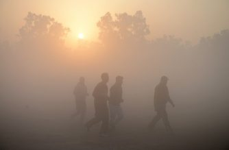 Indian people walk amid heavy smog conditions and fog as the sun rises in Jalandhar on November 30, 2018. - Smog levels spike during winter in northern India, when air quality often eclipses the World Health Organization's safe levels. Cooler air traps pollutants -- such as from burning garbage dumps, vehicles, construction sites and farmers burning crops -- close to the ground. (Photo by Shammi MEHRA / AFP)