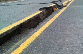 """People walk past a crack in the road after an earthquake near Northwoods on the Kenai Spur Highway in Kenai, Alaska on November 30, 2018. - A powerful earthquake rocked Anchorage, violently shaking homes and businesses in Alaska's largest city and knocking out power to some residents.The 7.0 magnitude quake was located about eight miles (13 kilometers) north of Anchorage and struck at 8:29 am local time (1729 GMT), the US Geological Survey said. (Photo by Caroline Huber / HANDOUT Caroline Huber / AFP) / RESTRICTED TO EDITORIAL USE - MANDATORY CREDIT """"AFP PHOTO /HO/ Caroline HUBER- NO MARKETING NO ADVERTISING CAMPAIGNS - DISTRIBUTED AS A SERVICE TO CLIENTS"""