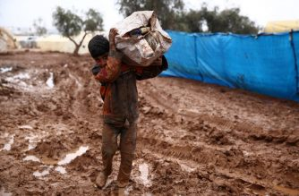 A Syrian boy carries a sack on his shoulder while walking in the mud at a camp for the displaced near the village of Shamarin, near the border with Turkey in the northern Aleppo province, on December 6, 2018. (Photo by Nazeer AL-KHATIB / AFP)