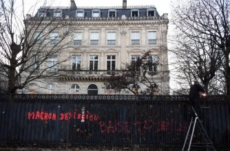 """A man is at work to repair the fence of an appartment building, on December 7, 2018 near the Champs-Elysees in Paris, on the eve of a fourth wave of """"yellow vests"""" anti-government protests. The graffiti reads """"Macron - Last Saturday's riots in Paris, where the Arc de Triomphe war memorial was sacked, dozens of cars torched and shops looted, were the worst in decades, plunging President Emmanuel Macron's government into a deep crisis. (Photo by Alain JOCARD / AFP)"""