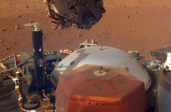"""In this image obtained from NASA, InSight's robotic-arm mounted Instrument Deployment Camera shows the instruments on the spacecraft's deck, with the Martian surface of Elysium Planitia in the background. The color-calibrated picture was acquired on December 4, 2018 - Humans can now hear the haunting, low rumble of wind on Mars for the first time, after NASA's InSight lander captured vibrations from the breeze on the Red Planet, the US space agency said on December 7, 2018. The strong gusts of wind, blowing between 10 to 15 mph (five to seven meters a second), were captured as they moved over the solar panels on InSight, an unmanned lander that touched down on Earth's dusty, desolate neighbor November 26. (Photo by HO / NASA/JPL-CALTECH / AFP) / RESTRICTED TO EDITORIAL USE - MANDATORY CREDIT """"AFP PHOTO / NASA/JPL-Caltech"""" - NO MARKETING NO ADVERTISING CAMPAIGNS - DISTRIBUTED AS A SERVICE TO CLIENTS"""