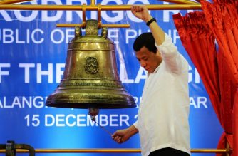 Philippine President Rodrigo Duterte raises a clenched fist as he rings one of the three Balangiga church bells during a ceremony in Balangiga in Eastern Samar province on December 15, 2018. - The sleepy central Philippine town of Balangiga erupted in joy on December 15 as bells looted from its church more than a century ago by vengeful US troops were turned over to the community, and rang once again on their home soil. (Photo by TED ALJIBE / AFP)