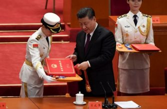 "China's President Xi Jinping prepares to award medals to people who received awards for contributing to China's development during a celebration meeting marking the 40th anniversary of China's ""reform and opening up"" policy at the Great Hall of the People in Beijing on December 18, 2018. - President Xi Jinping warned on December 18 that no one can ""dictate"" China's economic development path as the Communist Party marked 40 years of its historic ""reform and opening up"" policy amid a stern challenge from the United States. (Photo by WANG Zhao / AFP)"