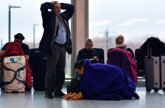 """A passenger rolls away a sleeping aid as she sits with their luggage in the South Terminal building at London Gatwick Airport, south of London, on December 21, 2018, as flights started to resume following the closing of the airfield due to a drones flying. - British police were Friday considering shooting down the drone that has grounded flights and caused chaos at London's Gatwick Airport, with passengers set to face a third day of disruption. Police said it was a """"tactical option"""" after more than 50 sightings of the device near the airfield since Wednesday night when the runway was first closed. (Photo by Ben STANSALL / AFP)"""