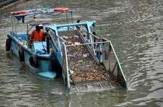 Sweeper boat cleans rubbish and plastics waste on a river in Singapore's financial district on June 29, 2018. (Photo by Roslan RAHMAN / AFP)