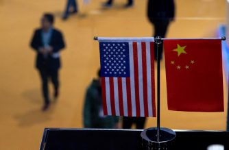 This picture taken on November 6, 2018 shows a Chinese and US flag at a booth during the first China International Import Expo (CIIE) in Shanghai. - There is a notable absentee among the dozens of national pavilions at a massive Chinese import fair -- the United States -- a no-show that underlines how Trump economic policies are causing trading partners to turn more toward China. (Photo by Johannes EISELE / AFP) / TO GO WITH AFP STORY US-CHINA-TRADE-DISPUTE-DIPLOMACY,FOCUS BY KELLY WANG AND DAN MARTIN