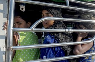 Rohingya Muslim women ride a police vehicle in Kyauktan township south of Yangon on November 16, 2018 after their boat washed ashore. - A boatload of Rohingya Muslims who left a camp in Myanmar's Rakhine state, arrived in Thante village in Kyauktan township on November 16 after they attempted to sail to Malaysia. (Photo by Hla-Hla HTAY / AFP)