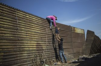 A group of Central American migrants climb the border fence between Mexico and the United States, near El Chaparral border crossing, in Tijuana, Baja California State, Mexico, on November 25, 2018. - Hundreds of migrants attempted to storm a border fence separating Mexico from the US on Sunday amid mounting fears they will be kept in Mexico while their applications for a asylum are processed. An AFP photographer said the migrants broke away from a peaceful march at a border bridge and tried to climb over a metal border barrier in the attempt to enter the United States. (Photo by Pedro PARDO / AFP)