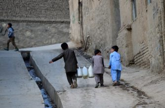 FILES: This photo taken on October 25, 2018 shows Afghan boys carrying containers of water to their home in Kabul. - A shortage of rain and snow, booming population and wasteful consumption have drained the Afghan capital's water basin and sparked a race to the bottom as households and businesses bore deeper and deeper wells in search of the precious resource. (Photo by WAKIL KOHSAR / AFP) / TO GO WITH: Afghanistan-climate-water, FEATURE by Laurent ABADIE