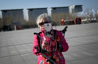 "This picture taken on December 26, 2018 shows retiree Wang Jinxiang live-streaming a performance outside the ""Bird's Nest"" national stadium in Beijing. - The 62-year-old is among a legion of senior citizens trying to make a name for themselves in China's massive social media scene, a world usually populated by the young. (Photo by WANG ZHAO / AFP) / TO GO WITH China-internet-elderly-lifestyle, FEATURE by by Pak Yiu"