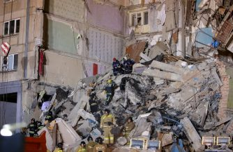 Emergency officers inspect rubble as they take part in a rescue operation after a gas explosion rocked a residential building in Russia's Urals city of Magnitogorsk on December 31, 2018. - At least four people were killed in the explosion and several dozen are missing. (Photo by STR / AFP)