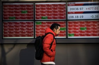 A pedestrian walks past a stock indicator board displaying share prices of the Tokyo Stock Exchange in Tokyo on January 7, 2019. - Tokyo stocks closed up more than two percent on January 7, 2019, after European and US markets roared last week on strong US data and dovish comments from the US Federal Reserve. (Photo by Behrouz MEHRI / AFP)