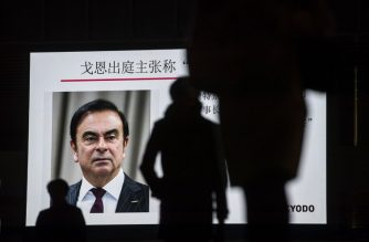 "Pedestrians pass by a television screen showing a news program featuring former Nissan chief Carlos Ghosn in Tokyo on January 8, 2019. - Former Nissan boss Carlos Ghosn said on January 8 he had been ""wrongly accused and unfairly detained"" at a high-profile court hearing in Japan, his first appearance since his arrest in November rocked the business world. (Photo by Behrouz MEHRI / AFP)"