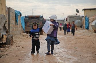 A displaced Syrian girl carries a box of emergency aid distributed to families in a makeshift camp for displaced people near the town of Atme close to the Turkish border in Syria's mostly rebel-held northern Idlib province on January 10, 2019, after more than a week of heavy rains and stormy weather. (Photo by Aaref WATAD / AFP)