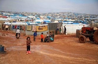 Children gather outside their makeshift shelters following torrential rain that affected a camp for displaced people near the town of Atme close to the Turkish border in Syria's mostly rebel-held northern Idlib province on January 10, 2019. - More than a week of heavy rains flooded flimsy plastic tents and turned nearby fields into pools of mud in the area. (Photo by Aaref WATAD / AFP)