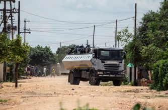Anti riot police stands on a truckload engaging in running battles with protestors in Emakhandeni township, Bulawayo, Zimbabwe on January 15, 2019. - The government more than doubled petrol prices at the weekend after months of shortages that saw drivers queueing for hours to fill up. Essentials such as bread and medicine have also been scarce. (Photo by ZINYANGE AUNTONY / AFP)