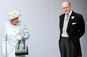 (FILES) In this file photo taken on October 12, 2018 Britain's Queen Elizabeth II (L) and Britain's Prince Philip, Duke of Edinburgh (R) wait for the carriage carrying Princess Eugenie of York and her husband Jack Brooksbank to pass at the start of the procession after their wedding ceremony at St George's Chapel, Windsor Castle, in Windsor, on October 12, 2018. - Queen Elizabeth II's 97-year-old husband Prince Philip emerged unscathed after being involved in a road traffic accident near the monarch's Sandringham Estate on January 17, 2019, Buckingham Palace said in a statement. (Photo by Alastair Grant / POOL / AFP)