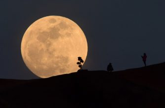 (FILES) In this file photo taken on January 30, 2018, a person poses for a photo as the moon rises over Griffith Park in Los Angeles, California. - The space agencies of the United States and China are in touch and coordinating efforts on Moon exploration, NASA said on January 18, 2019, as it navigates a strict legal framework aimed at preventing technology transfer to China. (Photo by Robyn Beck / AFP)