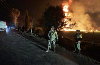 """This handout photo distributed by the Mexican Secretary of National Defence (Secretaria de Defensa Nacional) shows Mexican soldiers standing guard near a fire after a leaking gas pipeline triggered a blaze in Tlahuelilpan, Hidalgo state, on January 18, 2019. - A leaking fuel pipeline triggered a massive blaze in central Mexico, killing at least 20 people and injuring another 54, officials said. Omar Fayad, governor of Hidalgo state, said locals at the site of the leak were scrambling to steal some of the leaking oil when at least 20 of them were burned to death. (Photo by Handout / SECRETARIA DE DEFENSA NACIONAL / AFP) / RESTRICTED TO EDITORIAL USE - MANDATORY CREDIT """"AFP PHOTO / SECRETARIA DE DEFENSA NACIONAL """" - NO MARKETING NO ADVERTISING CAMPAIGNS - DISTRIBUTED AS A SERVICE TO CLIENTS"""