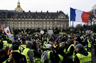 Protesters gather in front of the Hotel des Invalides to take part in an anti-government demonstration called by the Yellow Vest movement in Paris on January 19, 2019. - 'Yellow vest' protesters take to the streets on January 19 for 10th consecutive Saturday. (Photo by Philippe LOPEZ / AFP)
