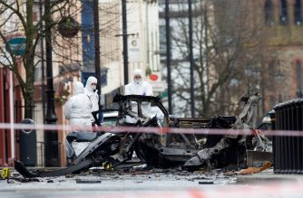Police forensic officers inspect the aftermath of a suspected car bomb explosion in Derry, Northern Ireland, on January 20, 2019. - A suspected car bomb exploded in the Northern Irish city of Derry (Londonderry) on January 19, police said, with leading politicians alleging the blast was terror-related. (Photo by Paul FAITH / AFP)
