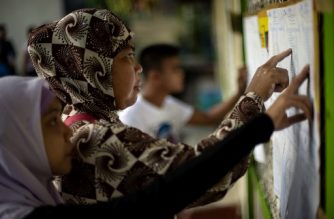 Muslim women look for their names at a voting precinct in Maguindanao, on the southern island of Mindanao on January 21, 2019, the plebiscite to ratify the passage of the Bangsamoro Organic Law (BOL). - A decades-long push to halt the violence that has claimed some 150,000 lives in the southern Philippines culminates with a vote on giving the nation's Muslim minority greater control over the region. (Photo by Noel CELIS / AFP)