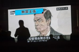 """(FILES) In this file photo taken on January 8, 2019, pedestrians walk past a television screen in Tokyo, showing a news programme displaying a sketch of former Nissan chief Carlos Ghosn in the courtroom as the headline reads in Japanese """"Innocence claim."""" - A Tokyo court on January 22, 2019 rejected a fresh bail request from ex-Nissan chief Carlos Ghosn, despite his pledge to stay in Japan if released before trial on financial misconduct charges. (Photo by Behrouz MEHRI / AFP)"""