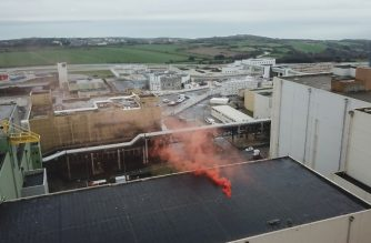 """This handout picture released and taken on January 25, 2019 in La Hague, Normandy, shows smoke billowing from an emergency flare which was dropped from a drone controlled by Greenpeace activists upon a roof of the Orano nuclear waste management facility, to denounce the """"vulnerability"""" of the site that contains, according to the NGO, the biggest radioactivity concentration in Europe. (Photo by Nicolas CHAUVEAU / GREENPEACE / AFP) / RESTRICTED TO EDITORIAL USE - IMAGE AVAILABLE FOR DOWNLOAD BY EXTERNAL MEDIA FOR 14 DAYS AFTER RELEASE - MANDATORY CREDIT """"AFP PHOTO / GREENPEACE / NICOLAS CHAUVEAU"""" NO MARKETING NO ADVERTISING CAMPAIGNS - DISTRIBUTED AS A SERVICE TO CLIENTS - NO ARCHIVES 14 DAYS AFTER RELEASE /"""