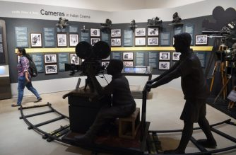 In this picture taken on January 22, 2019, an Indian student (R) visits the National Museum of Indian Cinema (NMIC), the country's first museum showcasing the history of its film industry, in Mumbai. - From silent black-and-white films to colourful blockbusters bursting with song and dance, a new museum tracing the evolution of Indian cinema has opened in the home of Bollywood. Costing 1.4 billion rupees (19.6 million USD), India's first national film museum is spread across a stylish 19th-century bungalow and a modern five-storey glass structure in south Mumbai. (Photo by PUNIT PARANJPE / AFP) / TO GO WITH AFP STORY INDIA-ENTERTAINMENT-FILM-BOLLYWOOD-HISTORY-MUSEUM,FOCUS BY UDITA JHUNJHUNWALA AND PETER HUTCHISON