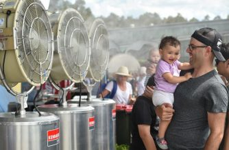 A father and his baby cool down in front of fans at the Sydney International tennis tournament in Sydney on January 11, 2017. - Sydney sweltered through scorching temperatures topping 40 Celsius (104 Fahrenheit) with beaches packed, bushfire warnings issued and people urged to stay hydrated. (Photo by PETER PARKS / AFP)