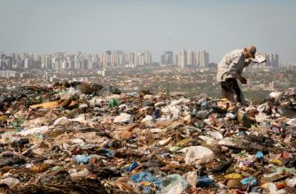 A waste picker, who are known as 'catadores de lixo' (garbage collector in Portuguese), searches for recyclable materials at Brasilia's garbage dump Lixao da Estrutural, considered as the largest in Latin America, on January 19, 2018. (Photo by Sergio LIMA / AFP)