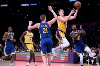 LOS ANGELES, CALIFORNIA - JANUARY 21: Moritz Wagner #15 of the Los Angeles Lakers scores on a layup past Jonas Jerebko #21 and Jordan Bell #2 of the Golden State Warriors during a 130-111 loss to the Golden State Warriors at Staples Center on January 21, 2019 in Los Angeles, California. NOTE TO USER: User expressly acknowledges and agrees that, by downloading and or using this photograph, User is consenting to the terms and conditions of the Getty Images License Agreement.   Harry How/Getty Images/AFP