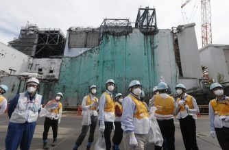 In this picture taken on July 27, 2018 and made available on July 30, 2018, foreign journalists receive information about decommissioning works between reactor unit 2 and unit 3 (in background) at the tsunami-crippled Tokyo Electric Power Company (TEPCO) Fukushima Dai-ichi nuclear power plant in Okuma, Fukushima prefecture. - The Fukushima nuclear disaster was triggered by a massive earthquake and ensuing tsunami in March 2011, which wrecked cooling systems at the plant on Japan's northeast coast, sparking reactor meltdowns and radiation leaks. (Photo by Kimimasa MAYAMA / POOL / AFP)