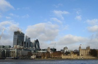 The Tower of London (R) is seen on the northern bank of the River Thames next to the office buildings and skyscrapers of the City of London (L) on December 21, 2018. - Staff at the Tower of London and other Royal Palaces held a strike over proposed changes to pension provision. (Photo by DANIEL SORABJI / AFP)