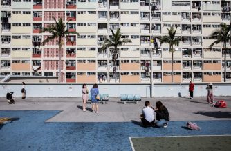 This picture taken on January 20, 2019 shows people sitting on a basketball court at a popular Instagram spot in Hong Kong. - For smartphone-wielding hordes of tourists, Hong Kong boasts a host of must-have Instagram locations -- but crowds of snap-happy travellers are testing local patience and transforming once quaint pockets of the bustling metropolis. (Photo by Isaac LAWRENCE / AFP) / TO GO WITH HongKong-lifestyle-tourism-photography, FEATURE by Elaine YU