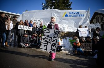 "Swedish youth climate activist Greta Thunberg (C) holds a placard next to students during a ""School strike for climate"" held on the sidelines of the World Economic Forum (WEF) annual meeting, on January 25, 2019 in Davos, eastern Switzerland. - Swedish 16-year-old Greta Thunberg has inspired a wave of climate protests by schoolchildren around the world after delivering a fiery speech at the UN climate summit in Katowice, Poland last month. (Photo by Fabrice COFFRINI / AFP)"