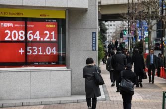 Pedestrians walk past the closing rate of the Tokyo Stock Exchange displayed in the window of a security company in Tokyo on February 12, 2019. - Tokyo stocks closed higher on February 12following reports that US lawmakers had agreed in principle to avoid a government shutdown, with the market also helped by a cheaper yen. (Photo by Toshifumi KITAMURA / AFP)