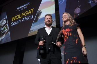 "Chef Kobus van der Merwe (L) receives the best Restaurant of the year award for his restaurant ""Wolfgat"" in South Africa during the inaugural World Restaurant Awards on February 18, 2019 at the Palais Brongniart in Paris. (Photo by Thomas SAMSON / AFP)"