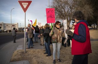 "People hold signs during a Presidents Day protest against the US president's national emergency declaration in downtown Las Cruces, New Mexico, on February 18, 2019. - The event is part of a national mobilization effort with protests to be held throughout the country. US President Donald Trump on February 15, 2019 invoked a ""national emergency"" to justify tapping military and other funds for barrier construction, after Congress approved less than a fourth the $5.7 billion he had sought for border security. (Photo by Paul Ratje / AFP)"