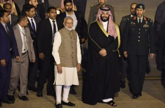 Saudi Crown Prince Mohammed Bin Salman stands next to Indian Prime Minister Narendra Modi (L) upon arriving at the airport in New Delhi on February 19, 2019. - Saudi Arabia's Crown Prince Mohammed bin Salman arrived in New Delhi on February 19 where his business mission threatened to be overshadowed by soaring tensions between India and Pakistan. The prince, who wants to persuade the world's fastest growing major economy to consume more Saudi oil, was greeted at the airport by Prime Minister Narendra Modi who gave his traditional bear hug for honoured guests. (Photo by Money SHARMA / AFP)