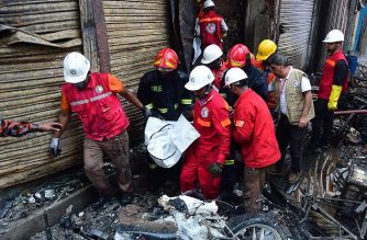 Rescue personnel carry the body of a victim after a fire broke out in Dhaka on February 21, 2019. - At least 69 people have died in a huge blaze that tore through apartment buildings also used as chemical warehouses in an old part of the Bangladeshi capital Dhaka, fire officials said on February 21, 2019. (Photo by Munir UZ ZAMAN / AFP)