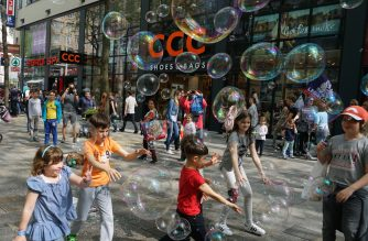 Children run after soap bubbles in the Mariahilfer street in Vienna, Austria, on May 6, 2017. (Photo by JOE KLAMAR / AFP)