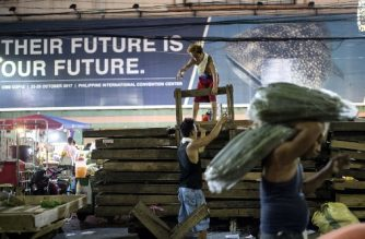 (File photo) Philippine workers arrange wooden palettes at Divisoria Market in Manila on November 29, 2017. (Photo by NOEL CELIS / AFP)