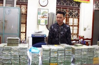 This handout taken by the Vietnam News Agency on February 25, 2018 and distributed on February 26 shows alleged drug smuggler and ringleader, Tran Van Bang, 31, standing before heroin bricks seized in the northern province of Cao Bang. Five men were arrested in Vietnam for allegedly attempting to smuggle 2.5 million USD worth of heroin into China after police shot at their drug-packed vehicle as they tried to flee, local media reported on February 26. / AFP PHOTO / Vietnam News Agency / Vietnam News Agency