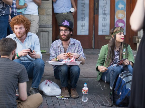 [UNVERIFIED CONTENT] Young, stylish hipsters sit on the curb while eating street food on 6th Street in Austin, Texas during SXSW 2013