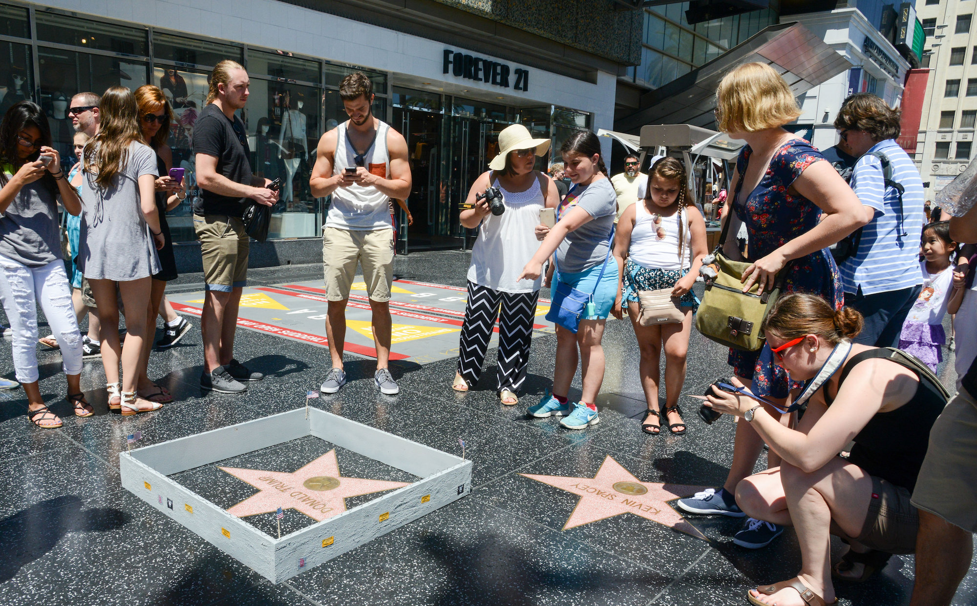 """Hollywood sightseeers on the famous walk of fame were confronted with an unusual edition to Trump's Famous Star. Someone had built a 6"""" tall grey concrete wall around it. Complete with """"Keep out"""" signs and topped with razor wire. The unofficial addtion to the iconic star appeared early Tuesday afternoon, to the amusement of onlookers. There was no word as to who created the humorous installation. However the miniture wall was adorned with """"STOP MAKING STUPID PEOPLE FAMOUS"""" which is believed to be the work of LA Street artist Plastic Jesus."""