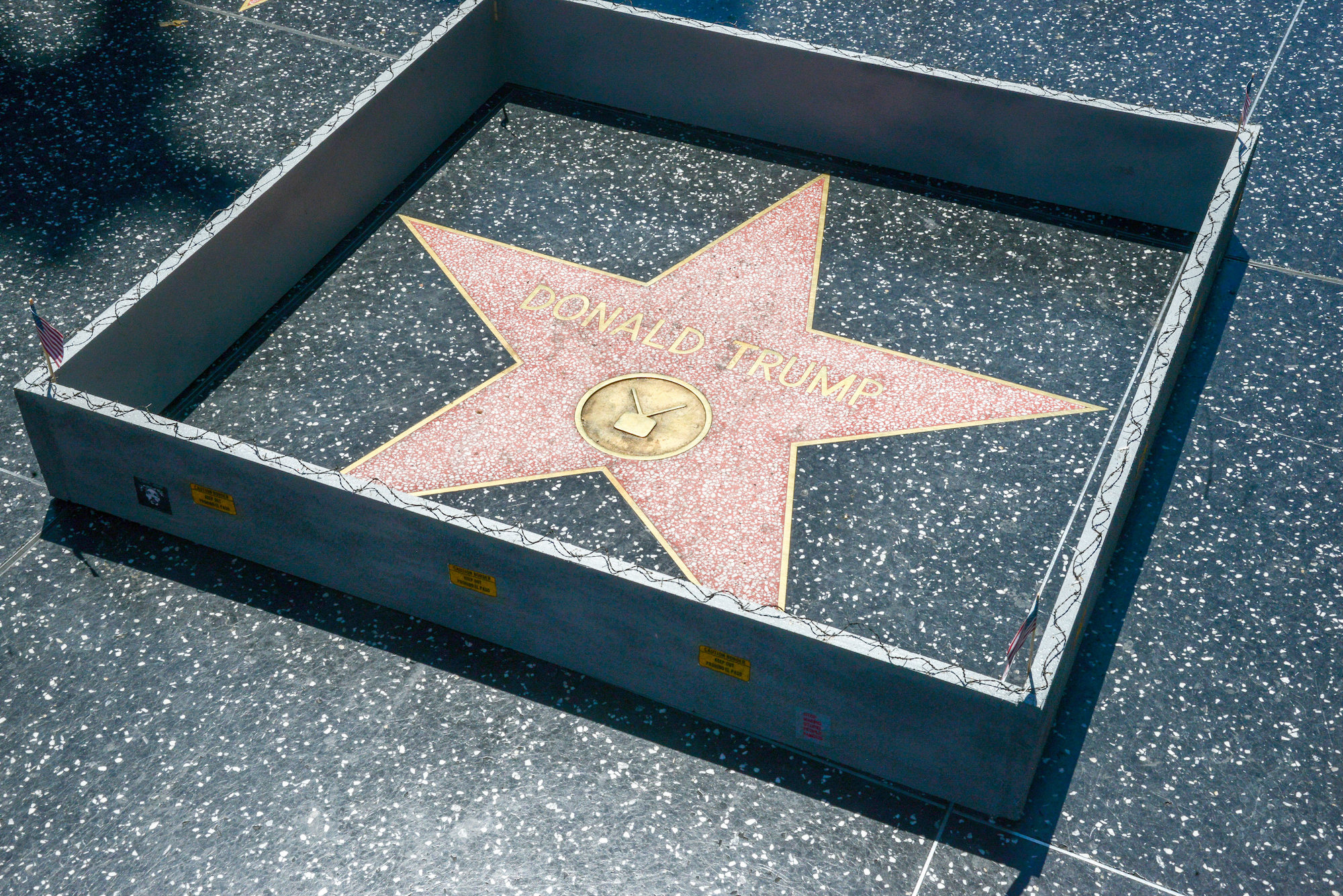 """Hollywood sightseeers on the famous walk of fame were confronted with an unusual edition to Trump's Famous Star. Someone had built a 6"""" tall grey concrete wall around it. Complete with """"Keep out"""" signs and topped with razor wire. The unofficial addtion to the icon star appeared early Tuesday afternoon, to the amusement of onlookers. There was no word as to who created the humorous installation. However the miniture wall was adorned with """"STOP MAKING STUPID PEOPLE FAMOUS"""" which is believed to be the work of LA Street artist Plastic Jesus."""